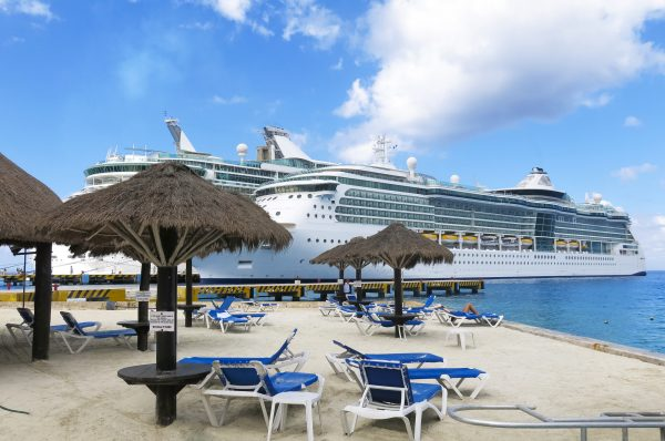 Two cruise ships docked next to a sandy beach with blue water and sky