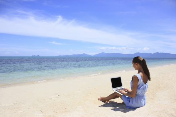 business lady sitting on beach working on laptop